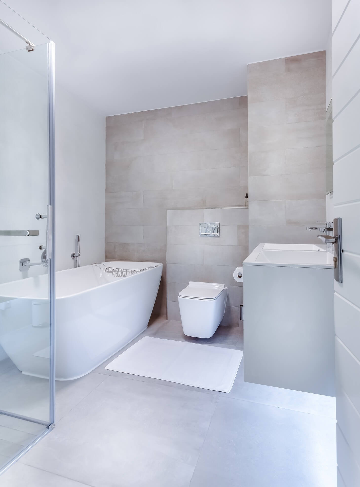 Highly minimalistic white-grey finish bathroom design with separate shower and standalone bathtub, toilet and double sinks