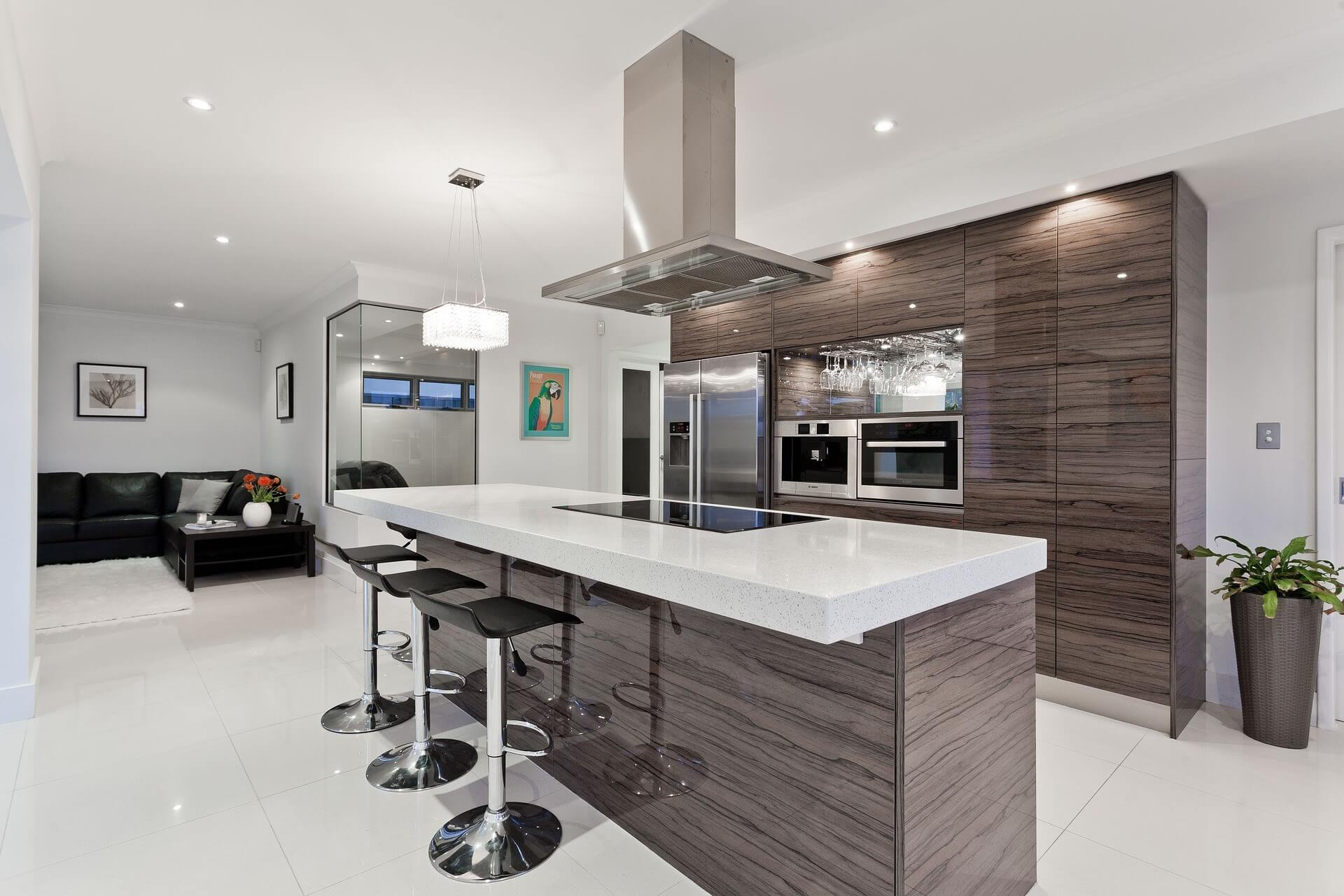 Luxurious open apartment kitchen design with island, high chairs, white tiling and a white and reflecting tree motif finish