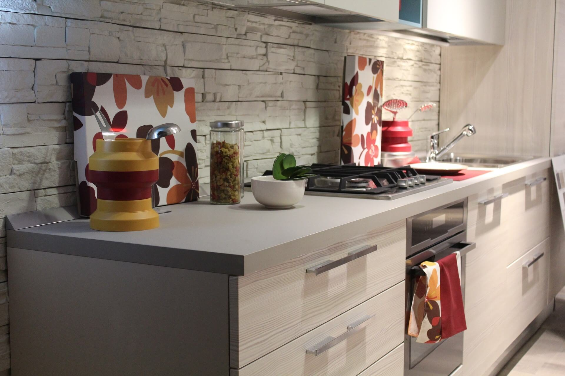 Warmly decorated light grey kitchen and natural white stones, with 70's style flower patterns and autumn colours