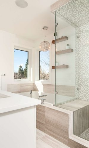 Natural and tiny square green-grey and white tiled bathroom with a small square bathtub, large cabin shower and two windows