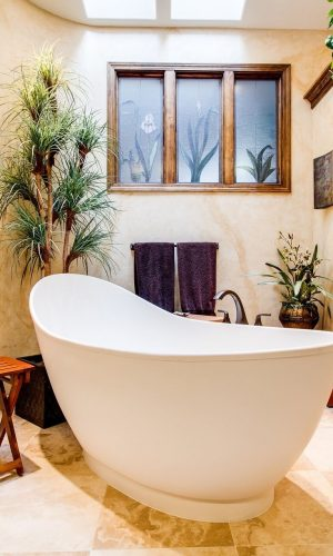 Natural coloured warmly decorated bathroom with paintings, a small table, scales, plants and a standalone bathtub