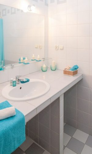 Tiled grey and white bathroom with teal decorations and candles